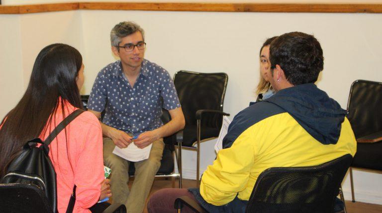 Tutor profesional del programa PACE UC sentado guiando a tres estudiantes UC, dispuestos en forma circular.