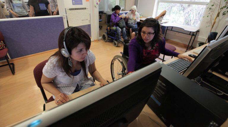 Dos estudiantes que participan del Programa para la Inclusión de Alumnos con Necesidades Especiales en las instalaciones del PIANE UC, sentadas en escritorio adaptado para la movilidad de estudiantes en silla de ruedas. Sobre el escritorio, computadores con softwares de apoyo a estudiantes con discapacidad.