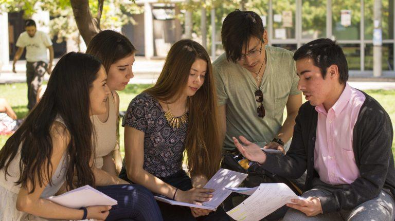Se encuentra un grupo de estudiantes reunidos en patio.