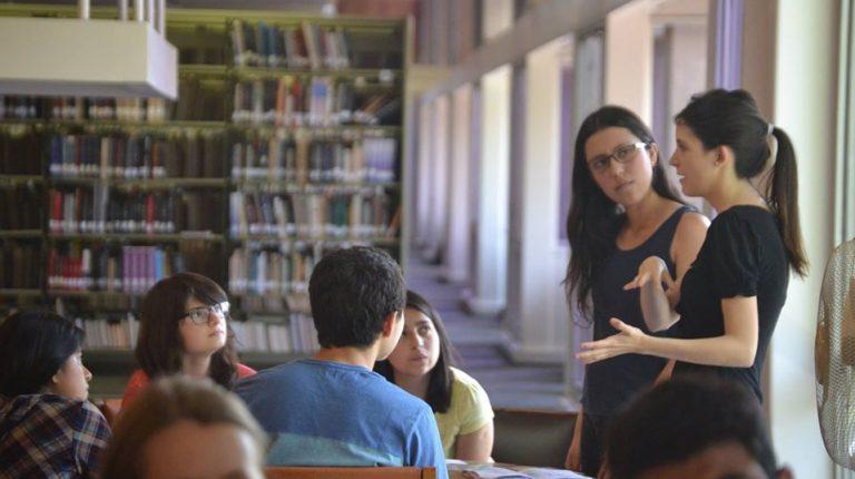 Se encuentran estudiantes en una mesa de la Biblioteca San Joaquín UC, conversando con profesor.