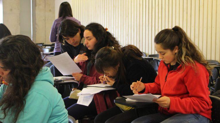 Se encuentran estudiantes realizando ejercicios en clase e interactuando con ayudantes.