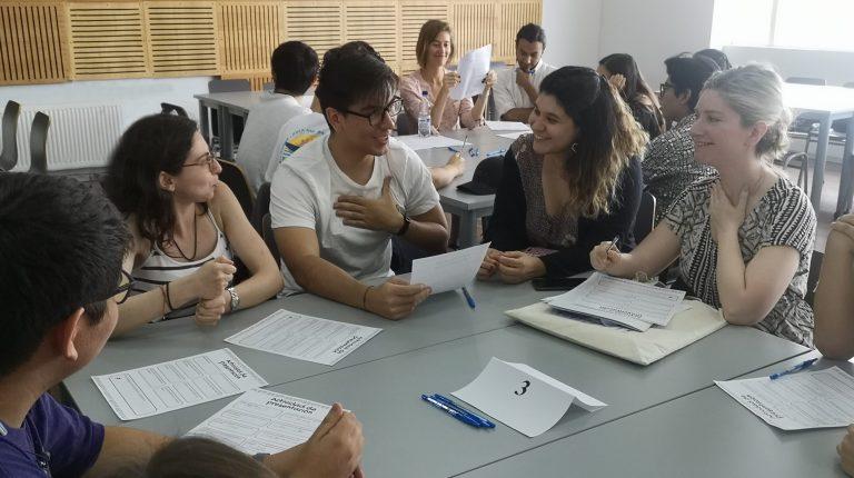 Grupo de estudiantes y profesionales, sentados en una mesa, conversando y sonriendo.