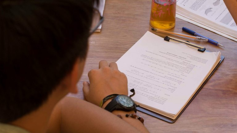 Estudiante con sus manos sobre una mesa y un cuadernillo.