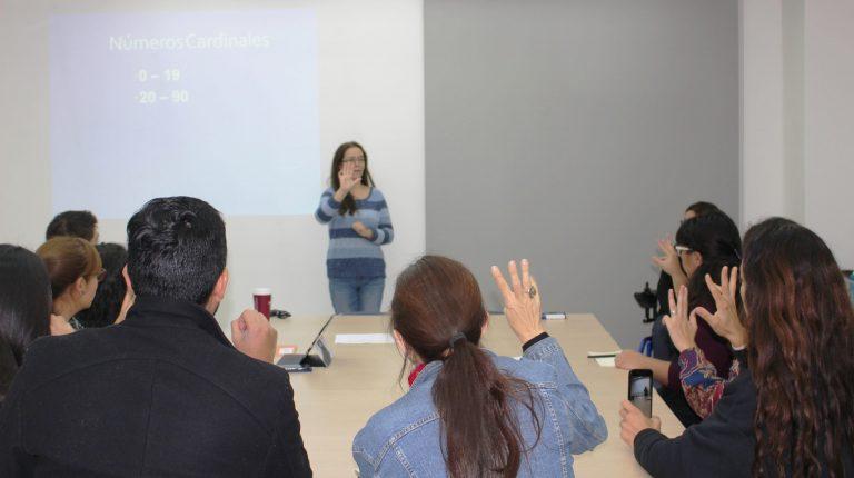 Profesores y profesoras en clase de Lengua de Señas Chilena haciendo una seña con su mano derecha que muestra la profesora al final de la sala.