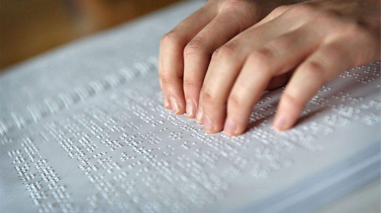 Manos sobre cuaderno con escritura en Braille.