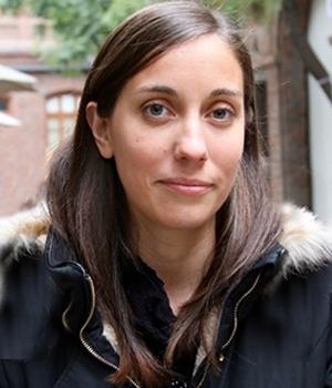 Foto facial de profesional de PACE UC, Beatriz Santelices, en fondo de edificio café.