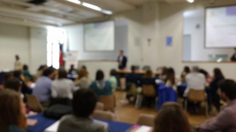 Se encuentra un grupo de personas en un auditorio. La imagen tiene un efecto borroso, no se distinguen rostros.