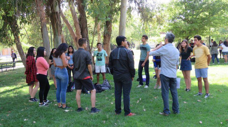 Estudiantes formando un círculo en explanada de pasto.