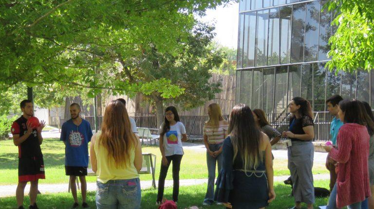 Estudiantes participando de una dinámica junto a profesionales de la Dirección de Inclusión y ayudantes parados en círculo en explanada de pasto frente a Edificio CDdoc del Campus San Joaquín.