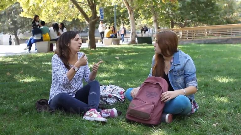 Estudiantes comunicándose en Lengua de Señas Chilena sentadas en pastos del Campus San Joaquín UC.