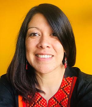 Foto facial de profesional de PACE UC, Yasna Castillo, en fondo mostaza.