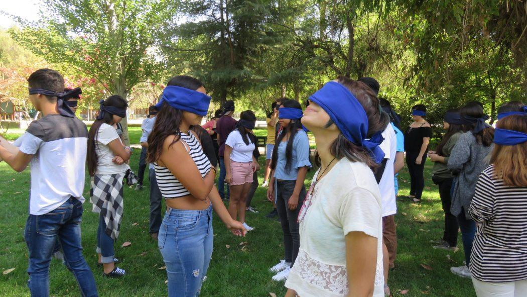 Estudiantes de primer año que ingresaron vía Cupo PACE UC en actividad de inserción en Campus San Joaquín, participando en una dinámica con vendas en sus ojos.