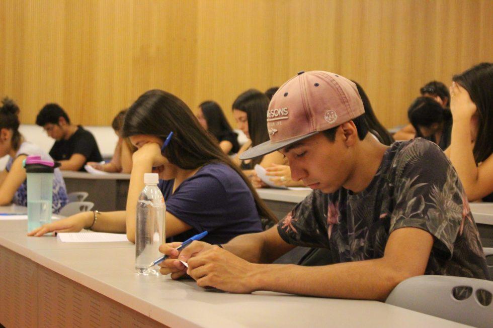 Estudiantes de primer año que ingresaron vía PACE UC rindiendo una prueba de diagnóstico de Lenguaje previo al ingreso en marzo en 2018 en una sala amplia, separados por un puesto.