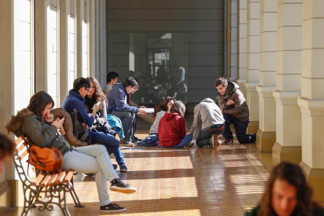 Fotografía de estudiantes estudiando y conversando, sentado en pasillo de Campus Casa Central. La foto cuenta con un mensaje escrito que dice 'Alertas Académicas + compromiso para mejorar tu desempeño académico'.
