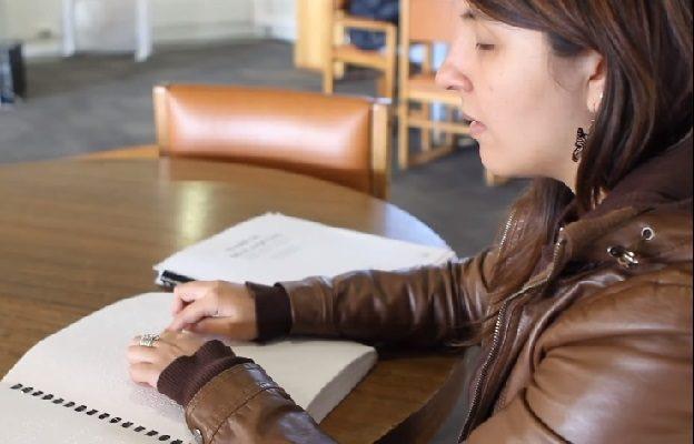 Estudiante ciega leyendo documento en Braille, sentada en mesa de la Biblioteca San Joaquín.