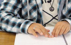 Manos de persona ciega leyendo documento en formato Braille.