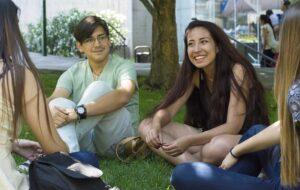 Estudiantes sentados en el pasto sonriendo.