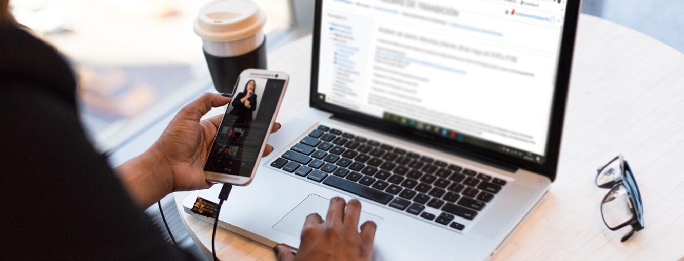 Persona frente a computador portátil, sosteniendo en una de sus manos un celular en el cual se visualiza a una intérprete en lengua de señas.
