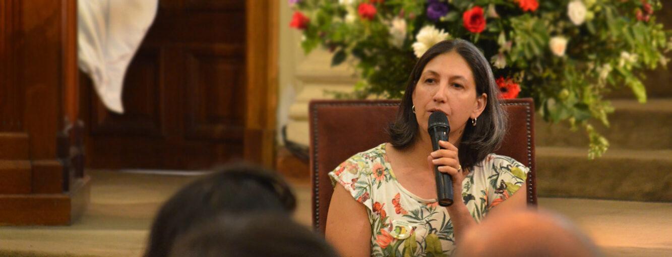 Catalina García, directora de Inclusión UC, en evento sosteniendo un micrófono