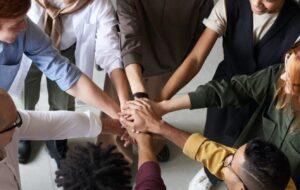 Diversas personas juntan sus manos en el centro