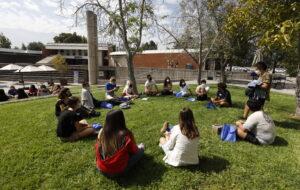 Estudiantes sentados en el pasto en campus UC