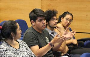 En la foto, se ven cuatro estudiantes UC conversando en encuentro intercultural, año 2019.