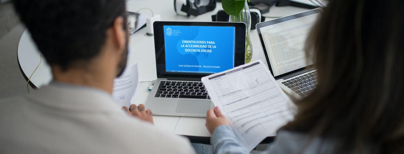 Dos personas de espaldas revisando papeles y de fondo un computador con el Manual de Orientaciones para la Accesibilidad de la Docencia online