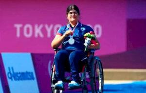 Mariana en silla de ruedas mostrando su medalla de plata ante las cámaras.