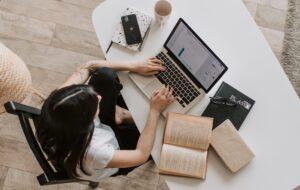 Vista desde arriba de una mujer sentada en una mesa, frente a computador, con un libro abierto a un costado.