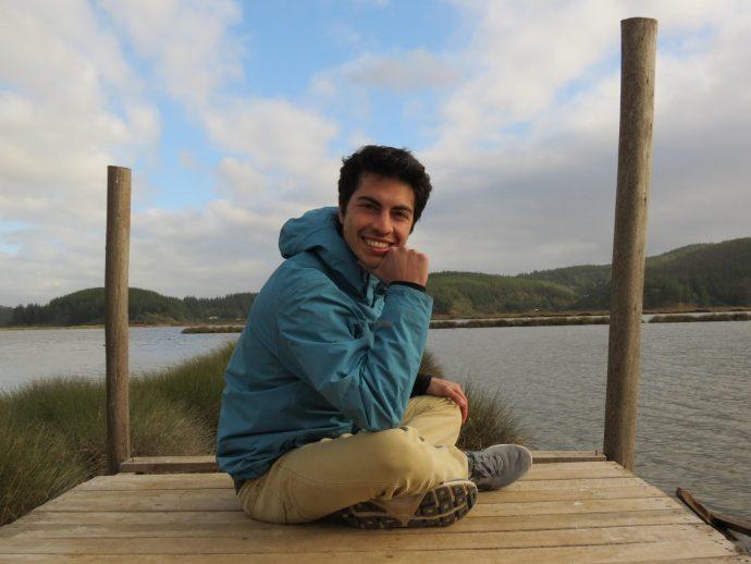 Ricardo Robles en la foto, sentado en un muelle, de fondo un lado al sur de Chile.