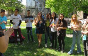Alumnos y alumnas de PACE UC sonriendo y aplaudiendo en actividad dirigida por tutora del programa, realizada en el patio exterior del edificio Cddoc en Campus San Joaquín.