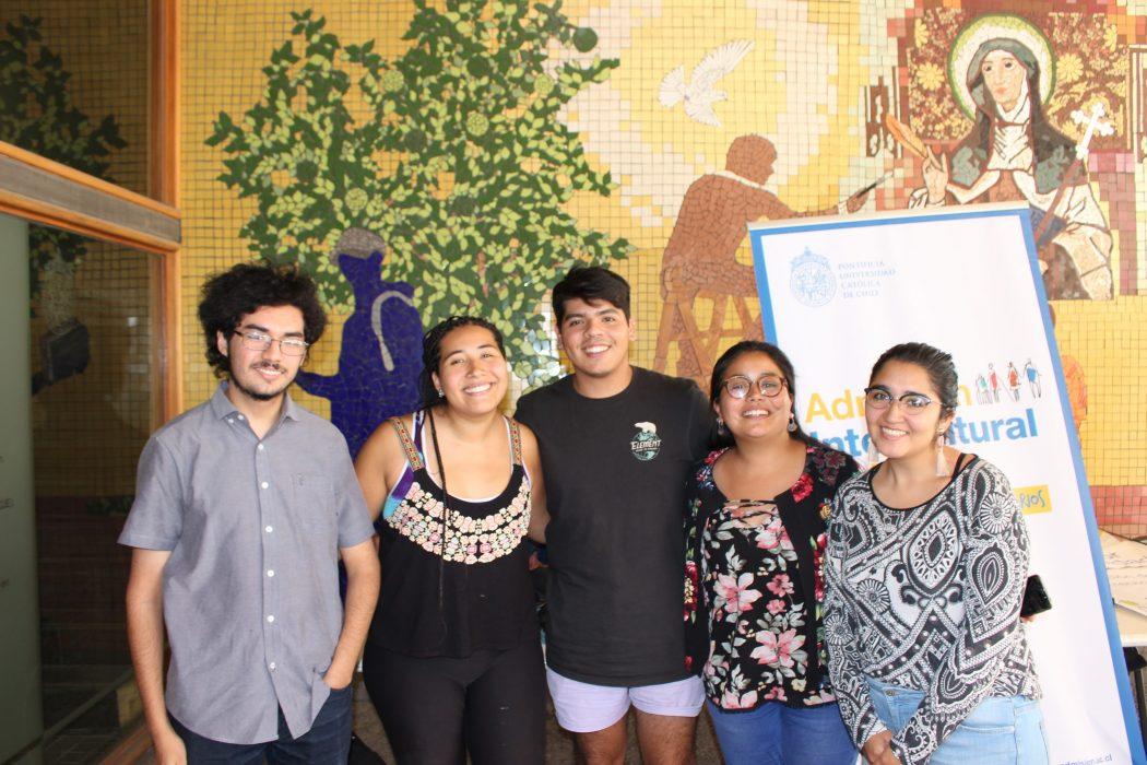 Cinco estudiantes de diversas carreras y culturas junto al pendón de la Vía Intercultural en la bienvenida al año universitario en 2019, para estudiantes migrantes y de pueblos originarios en la UC.