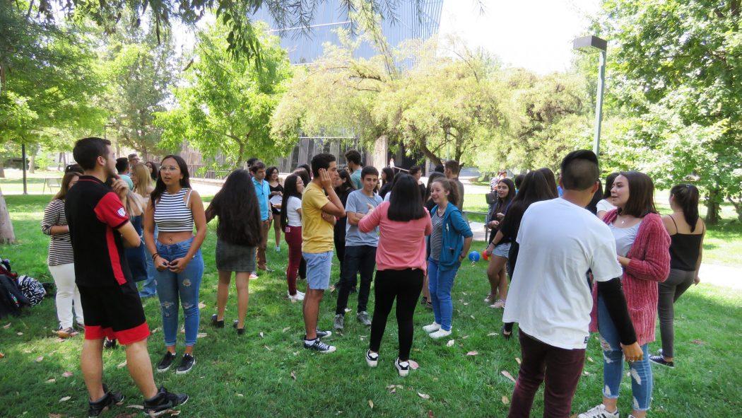 Estudiantes que ingresaron en 2019 por la vía Cupo PACE UC en explanada de Campus San Joaquín frente al Edificio Cddoc de pie realizando una actividad recreacional en grupos de dos y tres personas.
